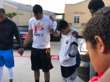 Jarrid prays with one of the student athlete's before heading to Clarskville, Texas for the basketball camp.