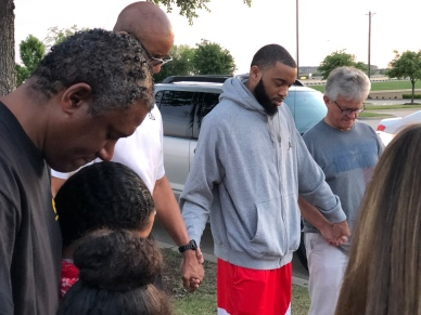 Coaches, parents, and kids pray before getting on the bus to Clarksville, Texas for the basketball camp.